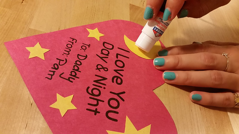 Glueing together a Night and Day Valentines Heart Craft for kids